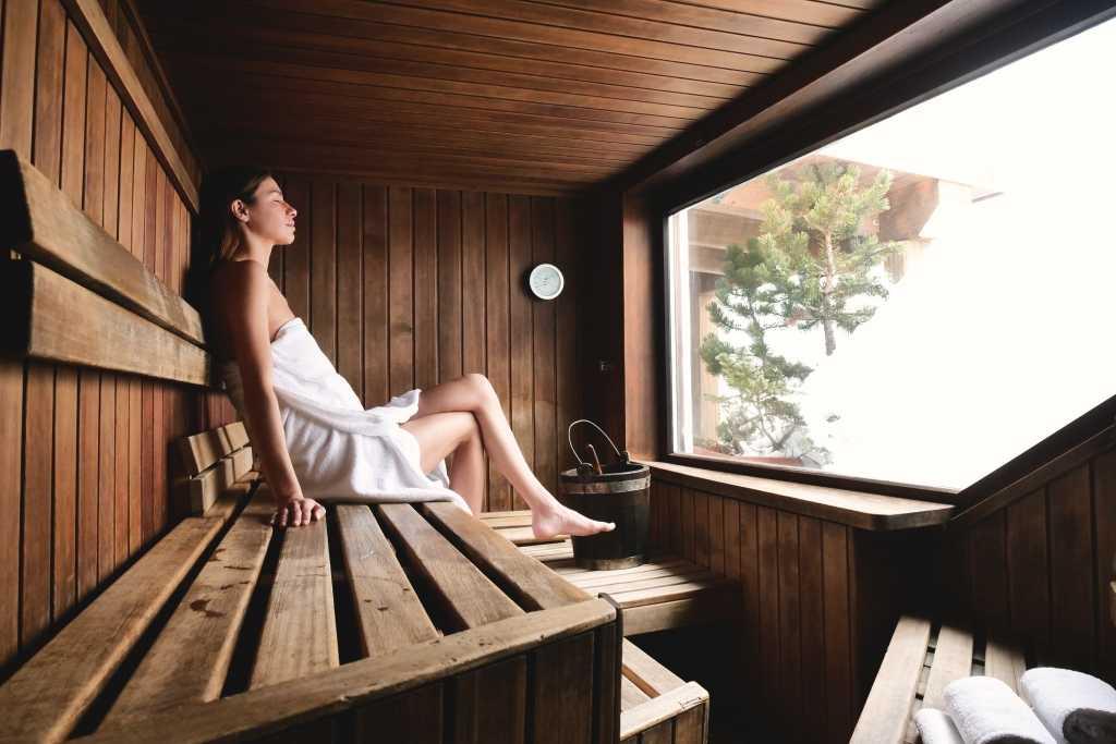 Entspannen in der Sauna. Frau sitzt in der Sauna im Garten