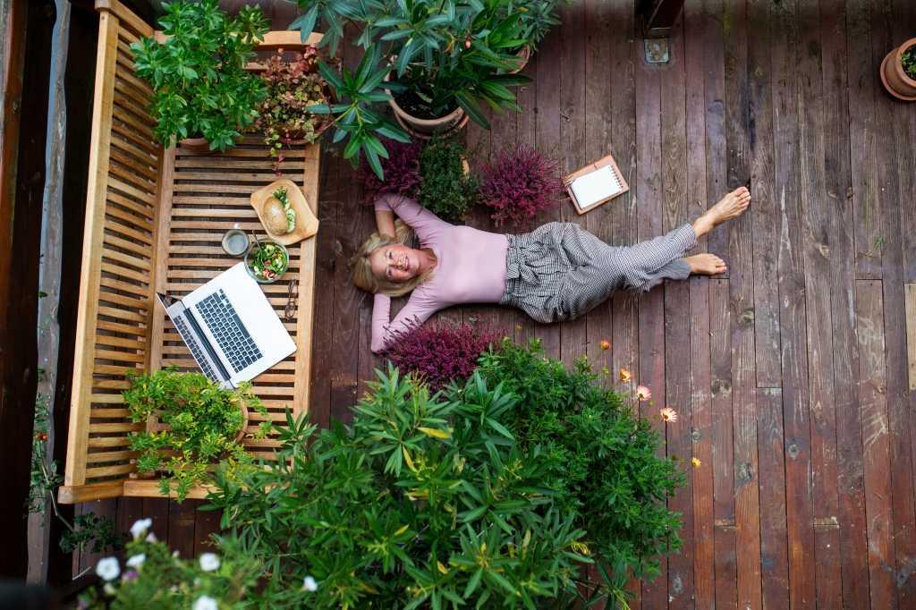 Seniorin entspannt auf eigener Terrasse mit Essen, Laptop und wirkt gelassen inmitten von Pflanzen.
